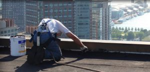 man repairing a flat roof overlooking the city