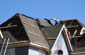 Construction workers putting shingles on the roof of a house.