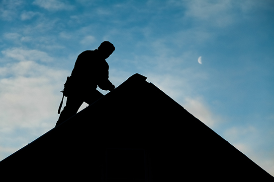 A man who is part of one of our roof maintenance programs, working on a roof.
